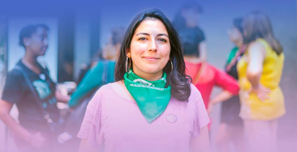 Photo of Alondra wearing a green bandanna, symbol of the abortion rights movement in Latin America.